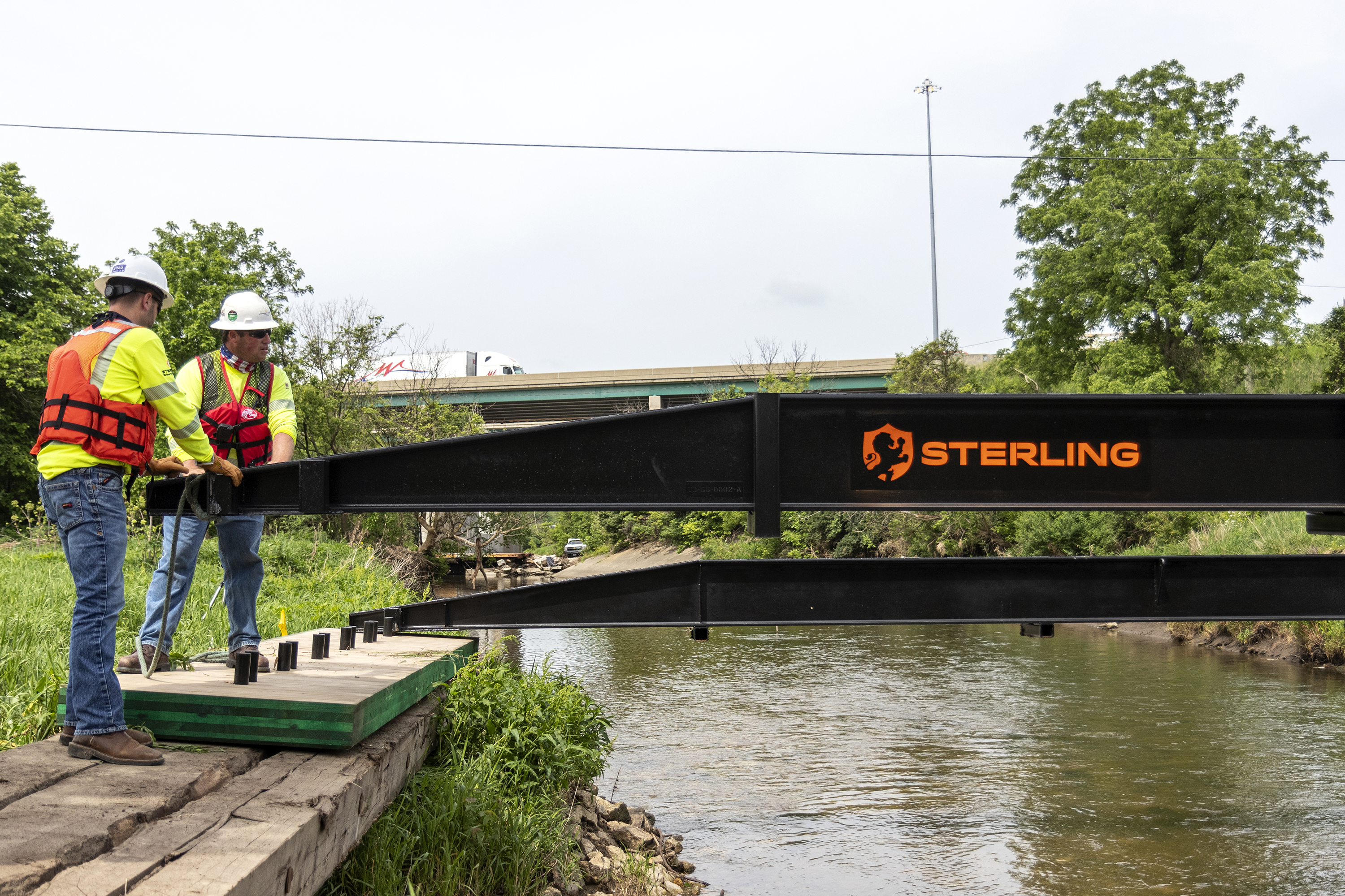 Two workers setting up a bridge over a river